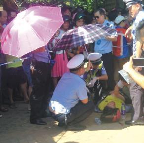 市民服务点中暑晕倒 海口交警撑伞遮烈日